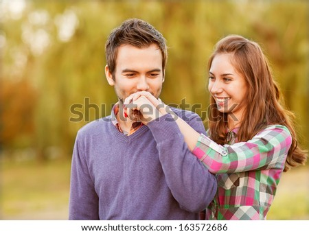 guy kisses the girl's hand in park - stock photo