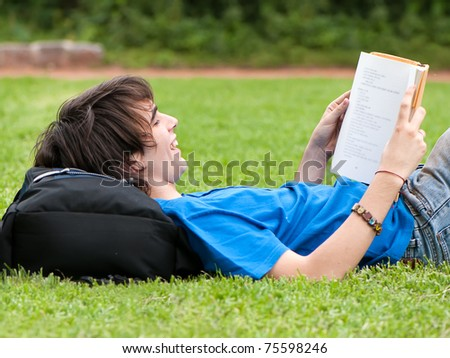 guy laying on the grass and reading a book - stock photo