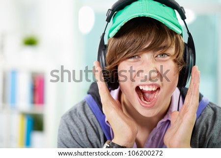 Guy listening to music screaming out loud emotionally - stock photo