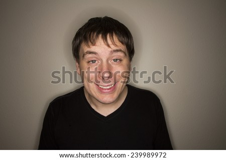 Guy looking at the camera with his eyes half open like he is stoned - stock photo