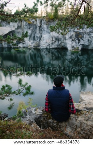 guy looks at the beautiful view from the cliff