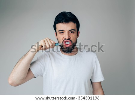 guy makes faces with toothbrush. Isolated on a light background