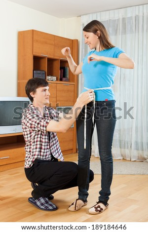 Guy measuring waist of girl with measuring tape - stock photo