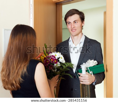 Guy meet his young woman with flowers at home door