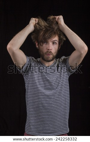 Guy messing up his hair. - stock photo