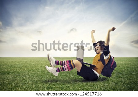 Guy on a large lawn with a backpack and a laptop rejoicing - stock photo