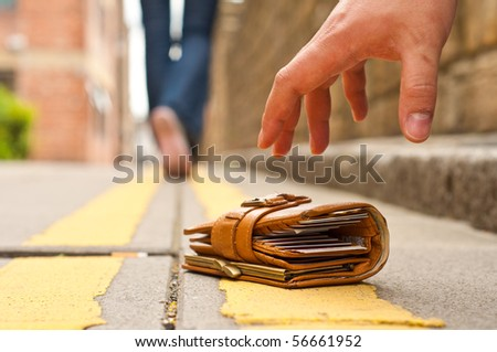 guy picking up a lost purce/wallet - stock photo