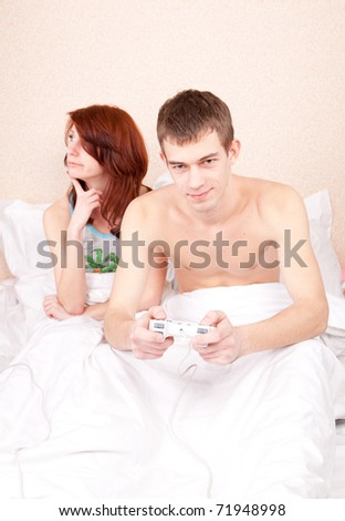 guy playing a video game in bed, she complains that she did not pay attention - stock photo