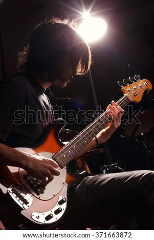 guy playing bass guitar. Rock music star. - stock photo