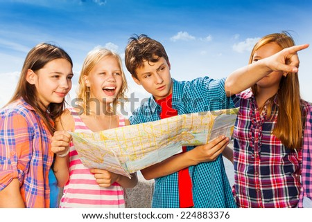 Guy points with other children standing together - stock photo