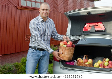 Guy puts apples harvest in the trunk of car - stock photo
