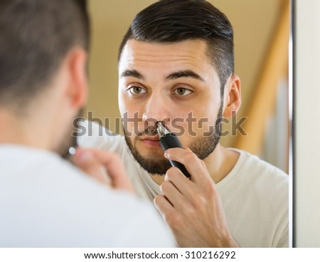 Guy remove hair from his nose and ears with trimmer