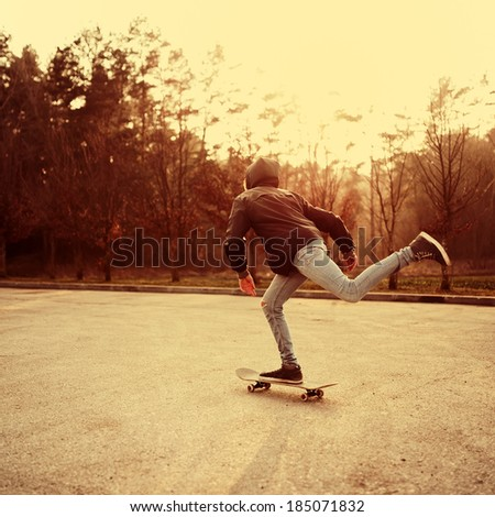 Guy rides on his skateboard at sunset