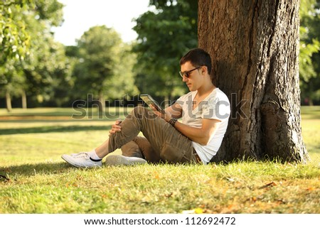 guy sitting beneath the tree using tablet - stock photo