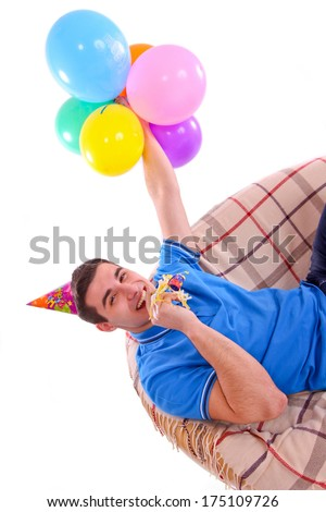 Guy sitting on the couch with a cap and balloons and whistling on the white background - stock photo