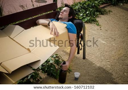 Guy sleeping off a tough hangover on a park bench - stock photo