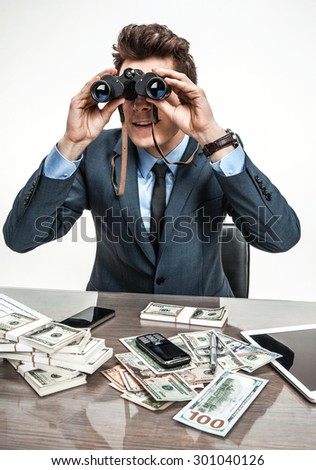 Guy spying with binoculars / photos of modern businessman at the workplace - stock photo