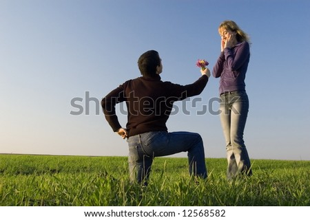 Guy stand on a knee and gives a bouquet to the girl - stock photo