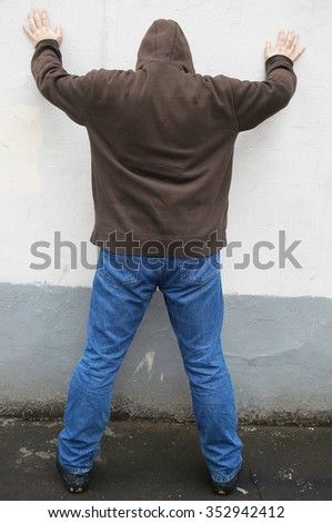 guy stands with his hands on a wall waiting for search incidental to the arrest