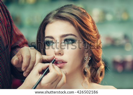 Guy stylist doing makeup beautiful woman in beauty salon with wavy hairstyle