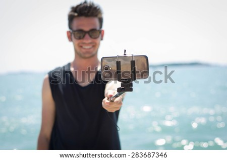 Guy take a selfie with his stick on his holiday at the beach - Lifestyle and technology concept - stock photo
