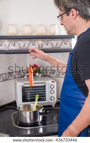 Guy throwing all sorts of vegetables in a pot - stock photo