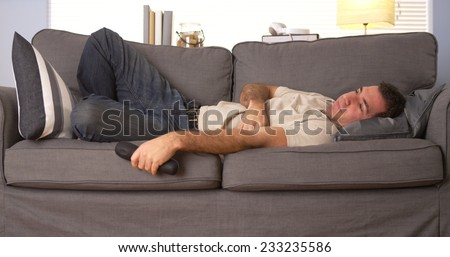 Guy trying to sleep on couch
