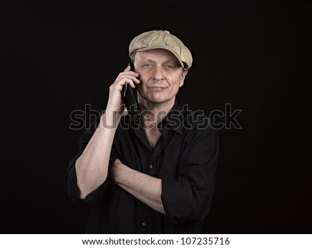 Guy using a mobile phone with copyspace on black - stock photo