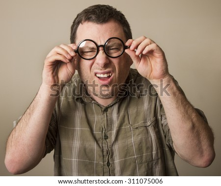 Guy who is wearing a pair of geek glasses squinting cause he can't see. - stock photo
