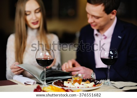 guy with a girl in a restaurant choose dishes from the menu - stock photo