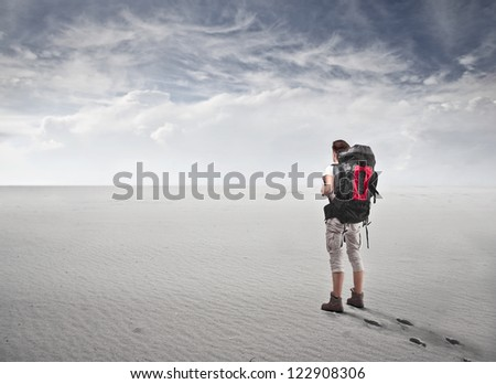 Guy with a travel backpack in a fake desert - stock photo