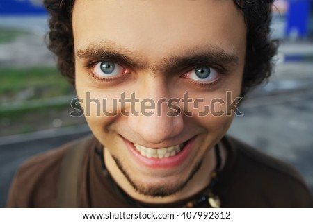 guy with crazy smile and big eyes, closeup - stock photo