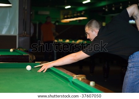 Guy with cue for the billiard table aiming to ball - stock photo