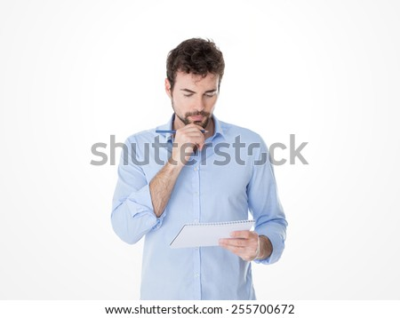 guy with hand on his chin reviewing his notes - stock photo