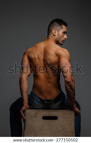 Guy with naked torso sitting on a podium. View from back. Grey background - stock photo