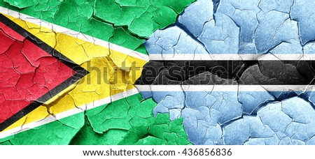 Guyana flag with Botswana flag on a grunge cracked wall