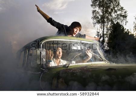 guys and car full of smoke - stock photo