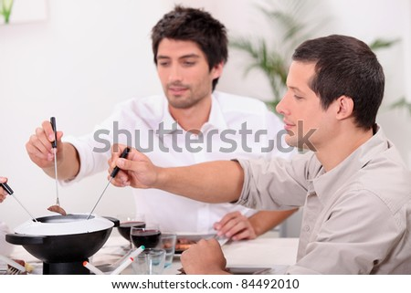 guys eating fondue - stock photo