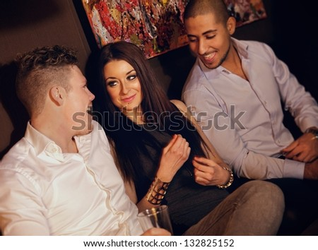 Guys hanging out with their female friend at the bar - stock photo