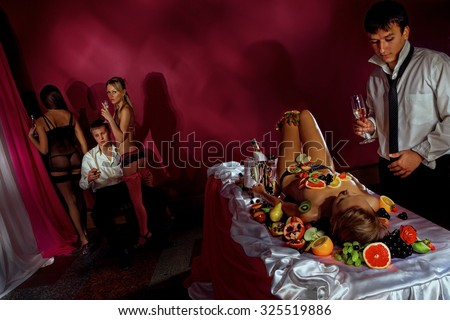 Guys having fun with woman decorated  by fruits and dancing stripteasers.  - stock photo