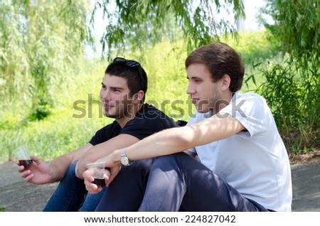 guys relaxing alongside a nature drink coffee - stock photo