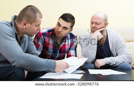 Guys sitting with papers and sharing problems
