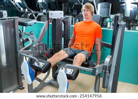 Gym blond man leg extension quadriceps exercise workout at indoor - stock photo