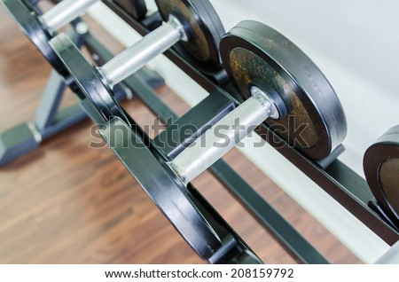 Gym equipment background with close up selective focus to a dumbbell - stock photo