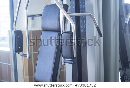 Gym exercise weight training pec deck chest resistance machine in fitness studio used to increase strength and build muscle.