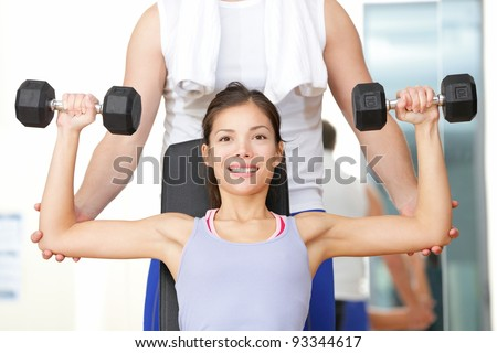 Gym fitness people - woman lifting weights with help from instructor and fitness trainer in gym. Beautiful smiling happy fit female fitness model training shoulders. - stock photo