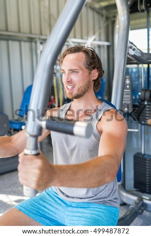 Gym fitness training. Male athlete training chest muscles on fitness equipment pec deck fly working out strength training indoors. Man working out pectoral muscles on fitness machine at gym center.