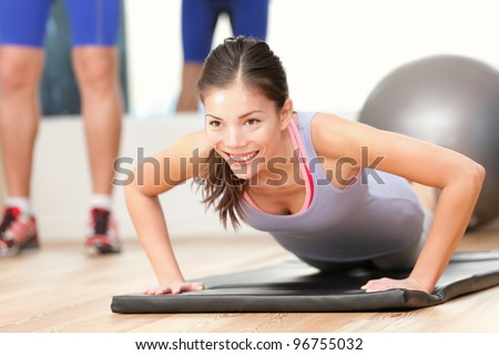 Gym fitness woman working out doing push-ups strength training smiling happy during workout. Young mixed race fitness model training in fitness center. - stock photo