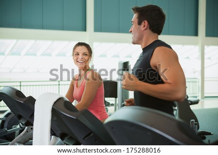 Gym: Friends Talk While Jogging On Treadmills - stock photo