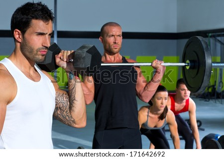 gym group with weight lifting bar and dumbbells workout in crossfit exercise - stock photo